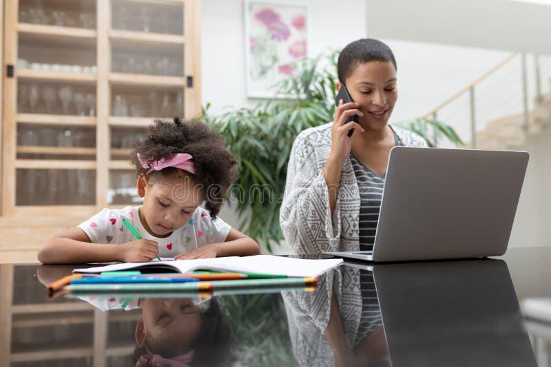 女孩做她的家庭作业,当母亲使用膝上型计算机和谈话在手机时 免版税库存照片