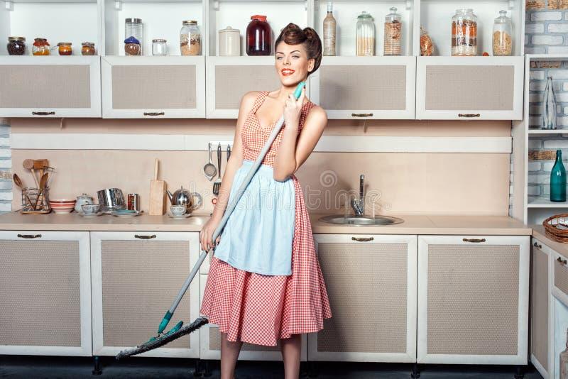 女孩做清洗厨房并且唱歌 免版税库存图片