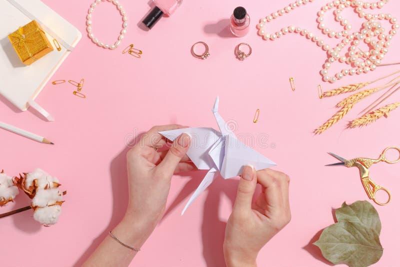 女孩做纸起重机origami 顶视图 免版税库存照片