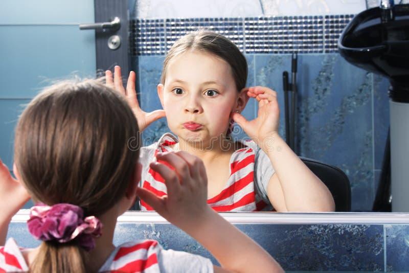 女孩做鬼脸的镜子 库存照片