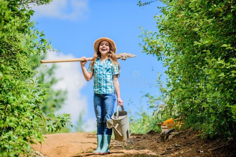 女孩儿童举行铁锹喷壶 春天从事园艺的清单小帮手 将解决干燥围场的浇灌的工具 库存照片