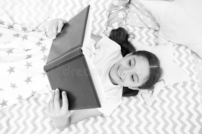 女孩儿童位置床读了书顶视图 鼓励有用的习性 孩子准备上床 宜人的时间在舒适卧室 库存图片