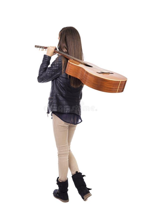 女孩全长画象有一把吉他的在她的肩膀, bac 免版税库存照片