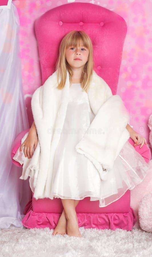 女孩公主坐桃红色王位 库存图片