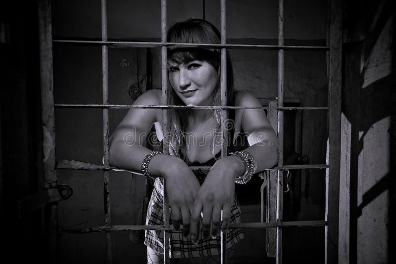 女孩关闭了关在监牢里,栅格,象在监狱 看性感在短裙 免版税库存图片