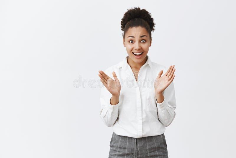 女孩兴奋解释了不起的新闻对工友,发笑和激动的谈话,打手势与棕榈 惊奇的快乐 库存照片