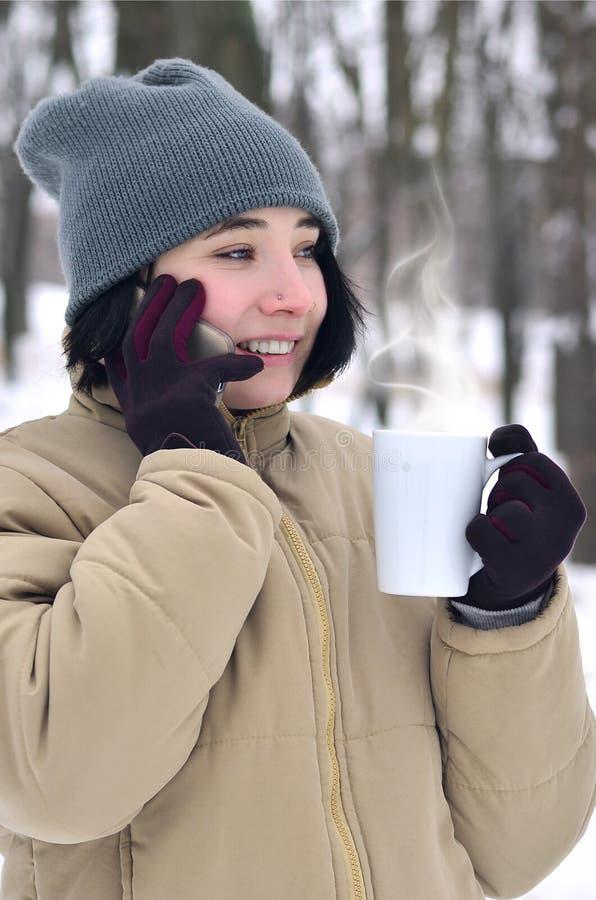 女孩冬天画象有智能手机和咖啡杯的 库存图片