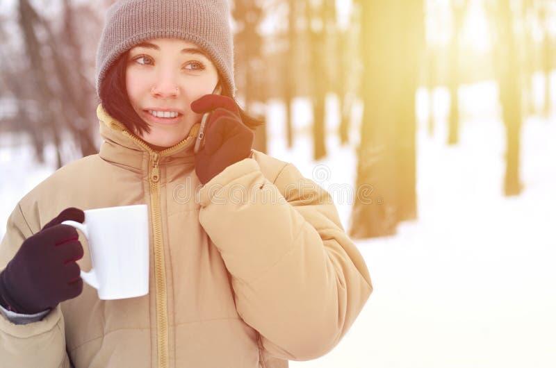 女孩冬天画象有智能手机和咖啡杯的 免版税库存照片