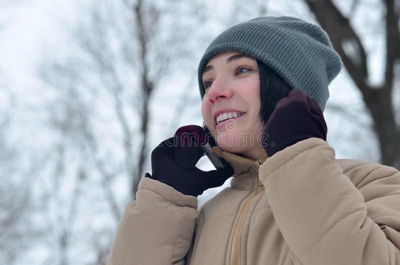 女孩冬天画象有智能手机的 免版税库存图片