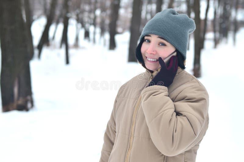 女孩冬天画象有智能手机的 免版税库存照片