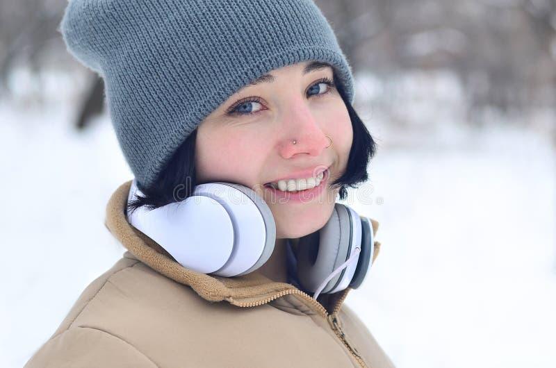 女孩冬天画象有耳机的 免版税库存图片