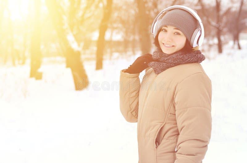 女孩冬天画象有耳机的 库存图片