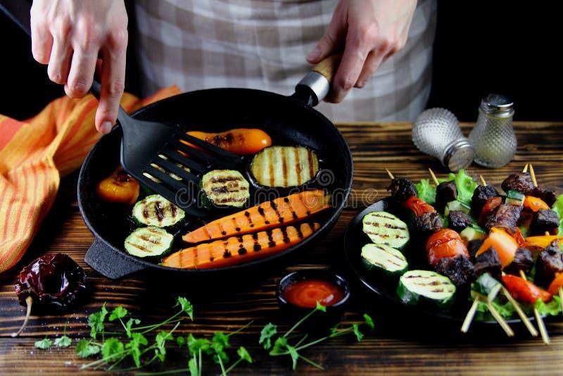 女孩准备在生铁长柄浅锅的烤菜 免版税库存图片