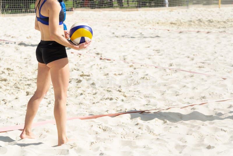 女孩准备服务在沙滩排球法院的球 免版税库存图片