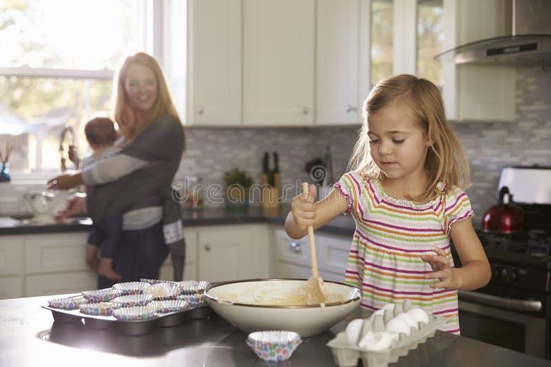 女孩准备蛋糕粉、妈咪和婴孩在背景中 免版税库存图片