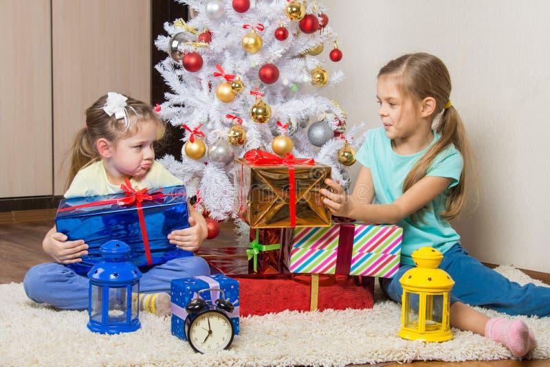 女孩分享出席的新年礼物在圣诞树 免版税库存图片