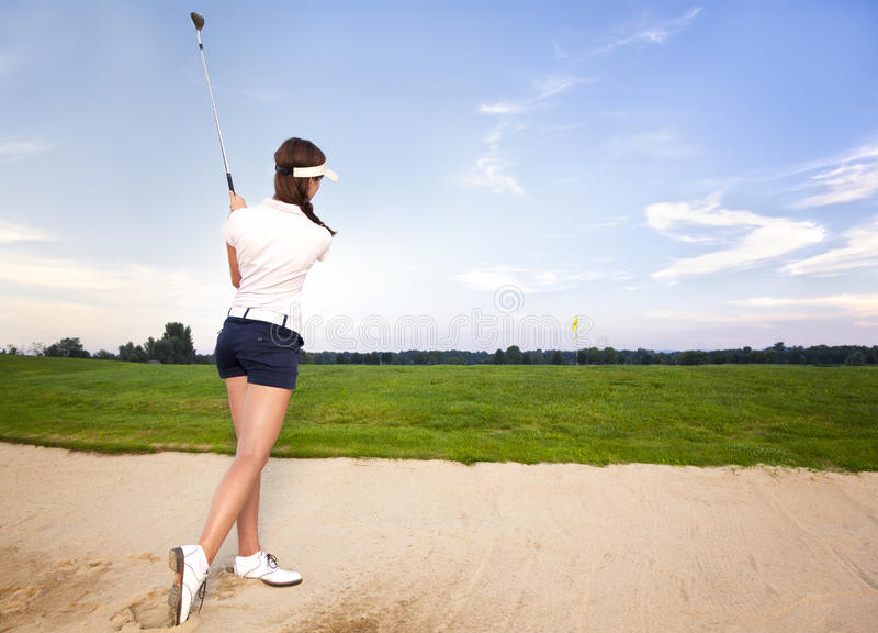 女孩切削球的地堡的高尔夫球运动员。 免版税库存图片