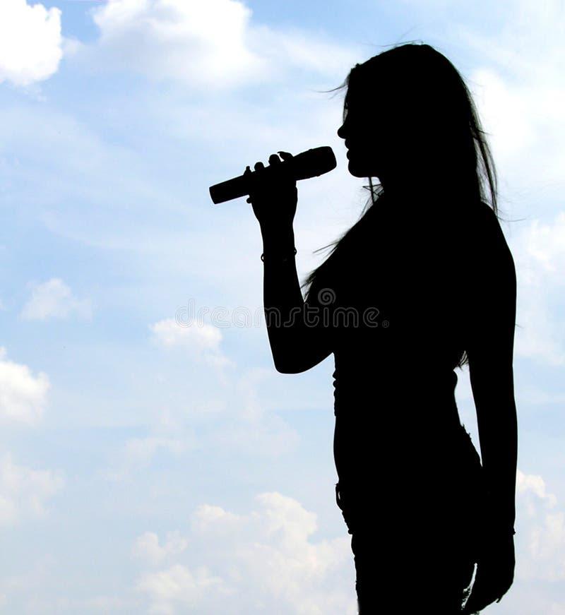 女孩剪影唱歌 库存照片