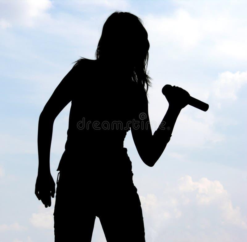 女孩剪影唱歌 图库摄影