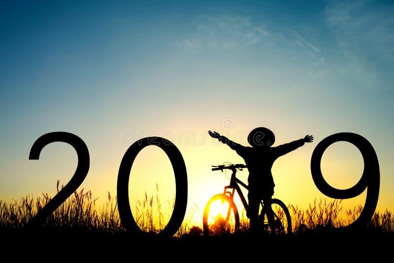 女孩剪影有自行车和2019词的 库存照片