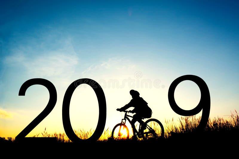 女孩剪影有自行车和2019词的 库存图片