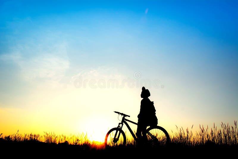 女孩剪影有自行车的在天空日落期间的领域 免版税库存图片