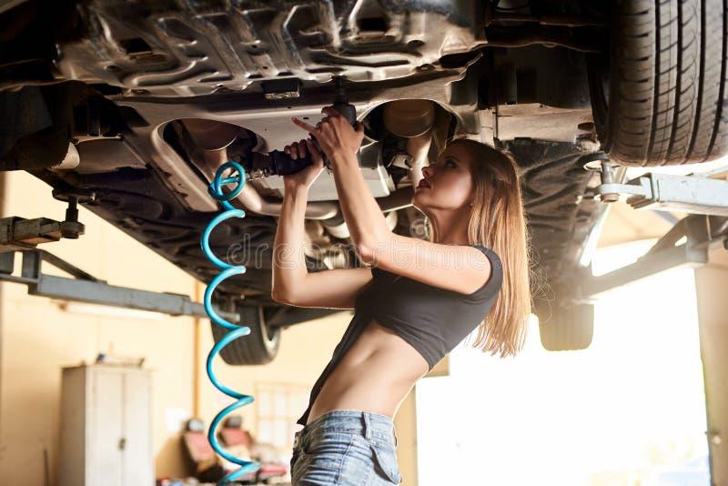 女孩加强汽车的底部的螺栓 库存图片