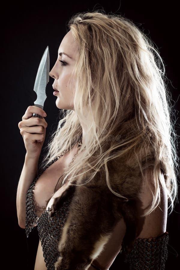 女孩北欧海盗或亚马逊 手中投掷的刀子 库存图片