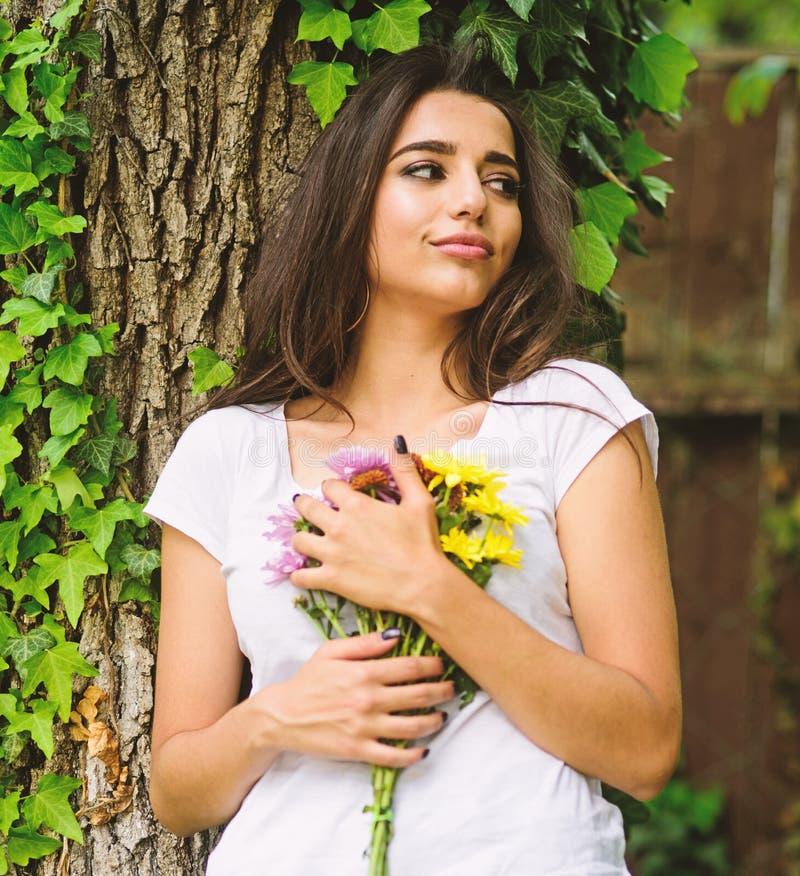 女孩华美的浅黑肤色的男人拥抱花束花,当在树干的倾斜与常春藤时 那是巨大日期 她得到了她的喜爱 免版税库存图片