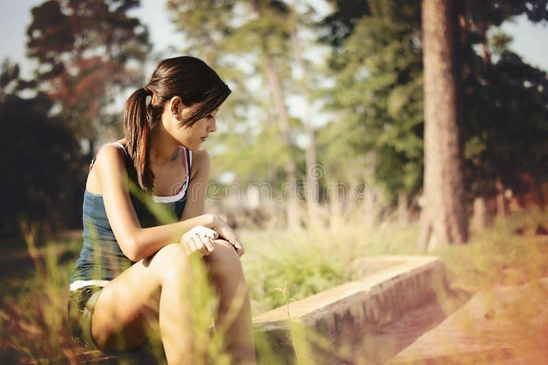 女孩单独认为在公园 免版税图库摄影