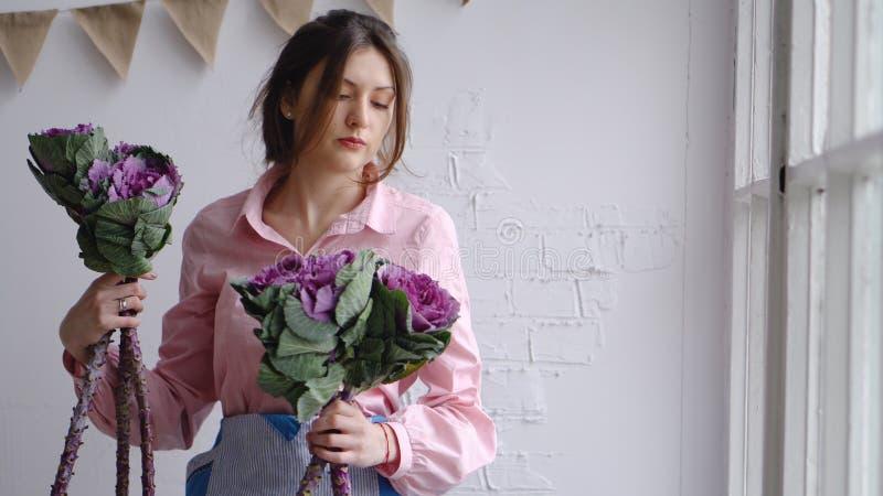 女孩卖花人选择最佳的花创造花束-装饰圆白菜 免版税库存照片
