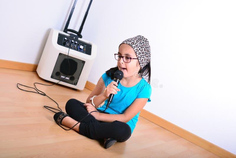 女孩卡拉OK演唱唱歌的一点 免版税图库摄影
