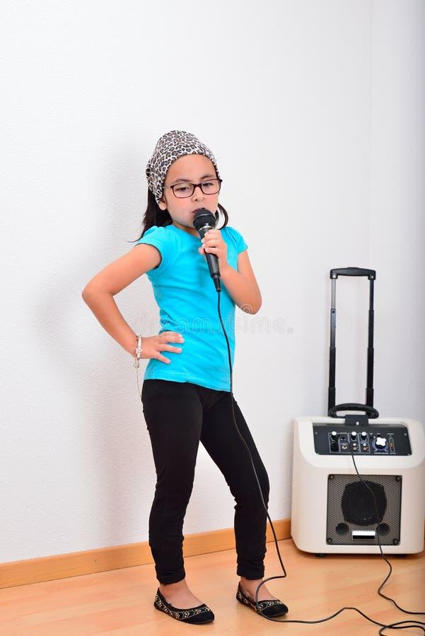 女孩卡拉OK演唱唱歌的一点 免版税库存照片