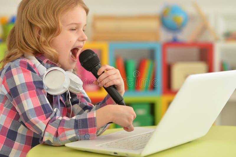女孩卡拉OK演唱唱歌的一点 库存图片