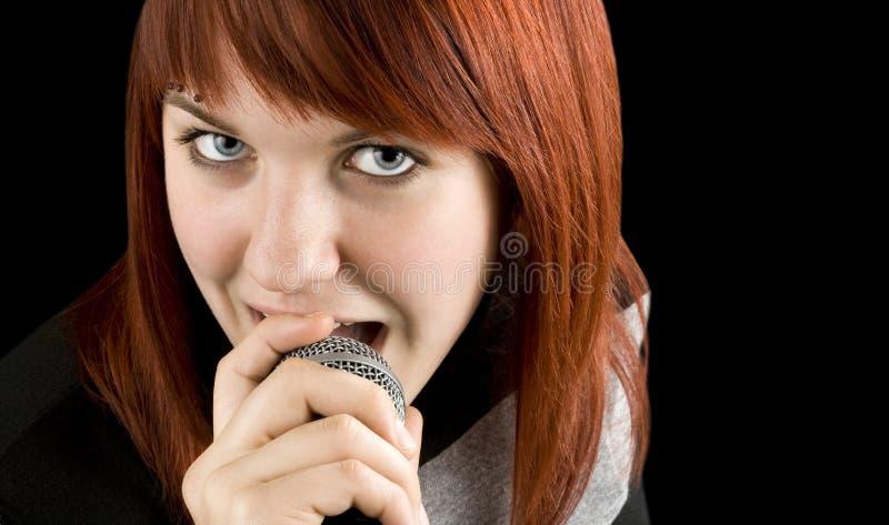 女孩卡拉OK演唱话筒唱歌 免版税库存照片