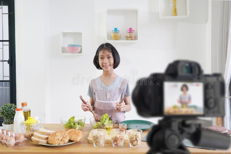 女孩厨师在家厨房里,当录音做录影博客作者照相机 库存照片