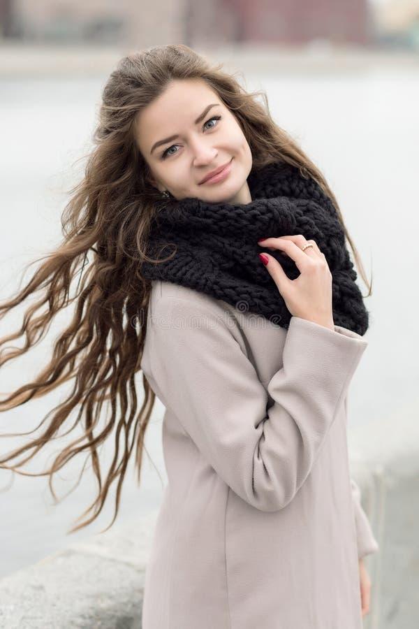 女孩发展在风的头发 一件黑外套、一条围巾和一件红色礼服的女孩反对灰色天空 没有 免版税图库摄影