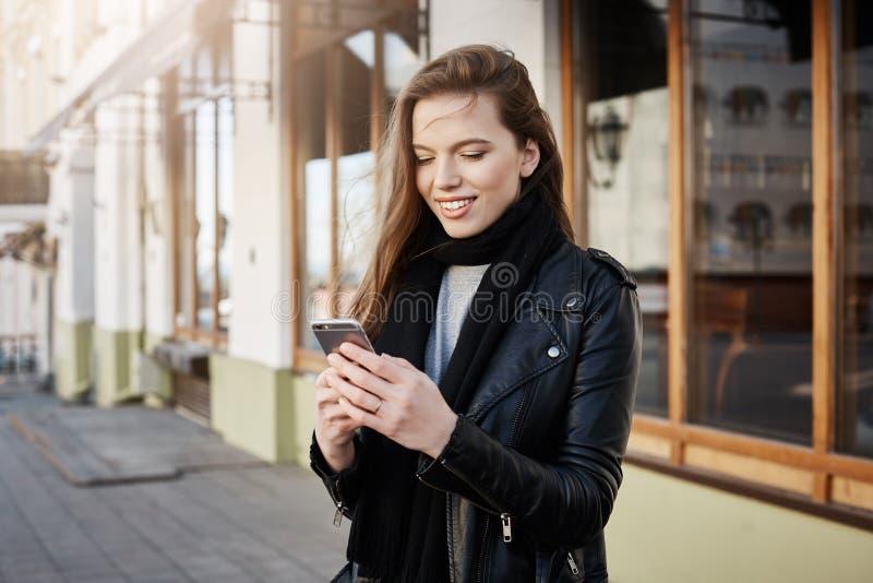 女孩叫出租汽车 拿着智能手机和看屏幕的时髦衣裳的美丽的现代妇女,当传讯时 免版税库存图片