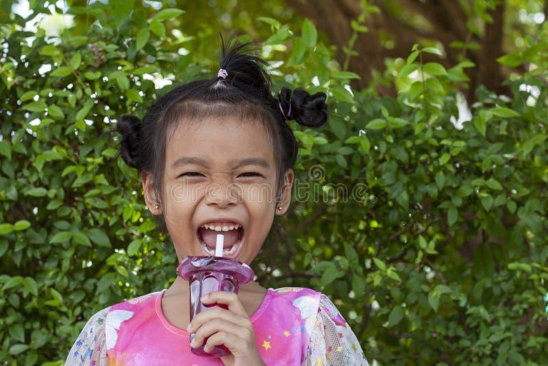 女孩吃在杯子塑料的甜果冻布丁与白色管 免版税图库摄影