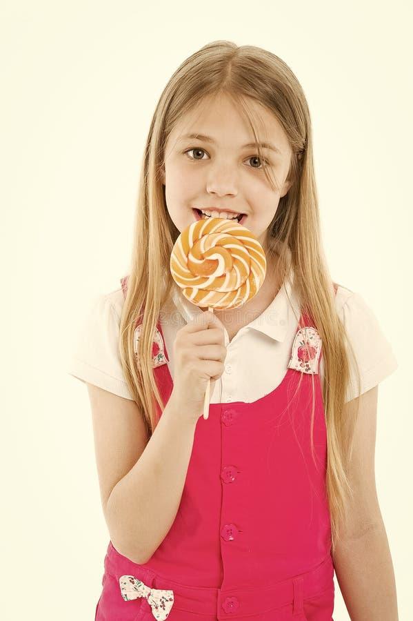 女孩吃在白色的棒棒糖 小孩享用在棍子的糖果 愉快的孩子微笑用漩涡焦糖 Candyshop 免版税图库摄影