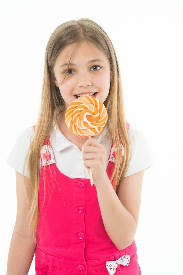 女孩吃在白色隔绝的棒棒糖 小孩享用在棍子的糖果 愉快的孩子微笑用漩涡焦糖 Candyshop 库存图片