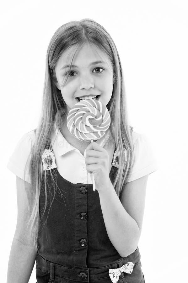 女孩吃在白色隔绝的棒棒糖 小孩享用在棍子的糖果 愉快的孩子微笑用漩涡焦糖 Candyshop 图库摄影