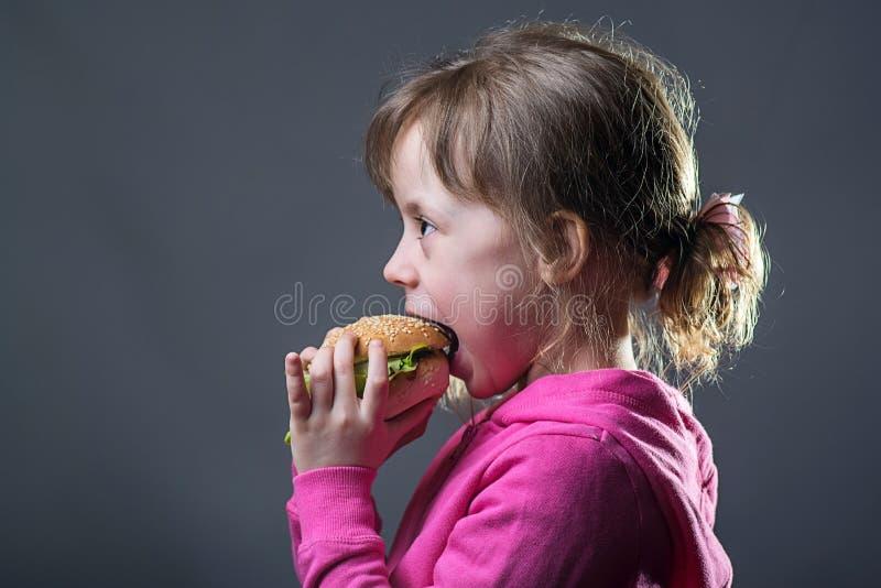 女孩吃快餐,在灰色背景的画象 图库摄影
