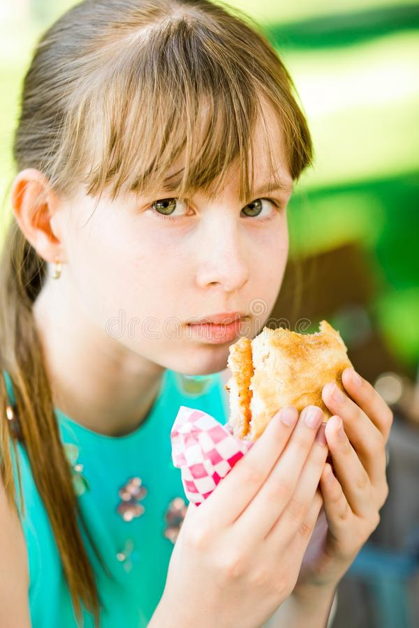 女孩吃汉堡包 库存照片