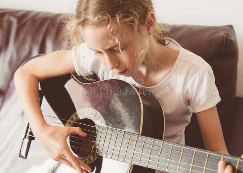 女孩吉他一点作用 免版税库存图片