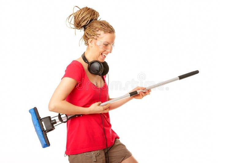 女孩吉他假装对年轻人的拖把作用 免版税库存照片