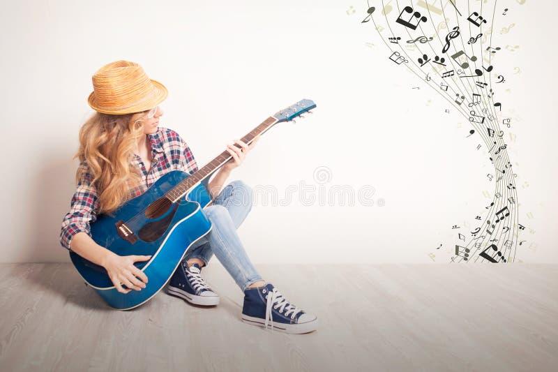 女孩吉他戏剧坐地板 免版税库存图片