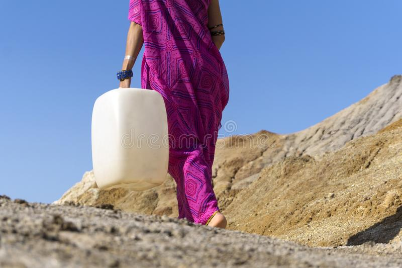 女孩向与jerrican的水求助 库存照片