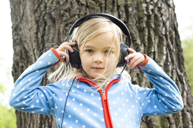 女孩听到在耳机的音乐 免版税库存照片