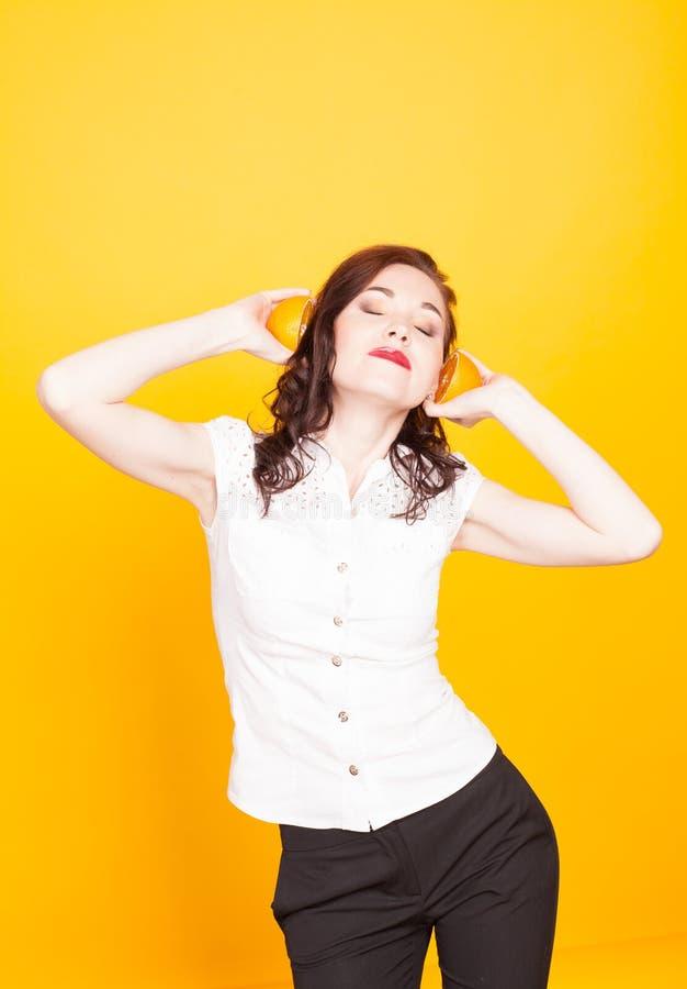 女孩听橙色一半作为音乐 免版税库存照片